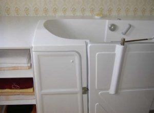 Baignoire à porte vallon avec rangements intégrés dans un meuble bonnetière