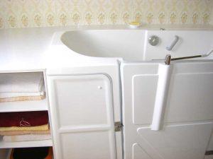 Baignoire à porte vallon avec meuble bonnetière